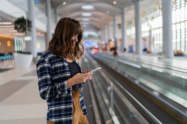 Vrouw die door de luchthaven loopt met haar smartphoneapparaat.