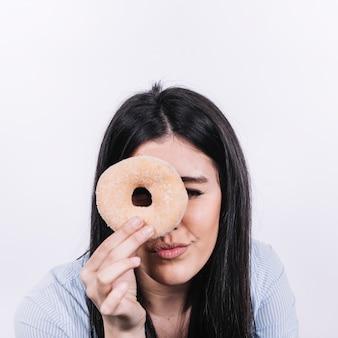 Vrouw die door doughnut kijkt