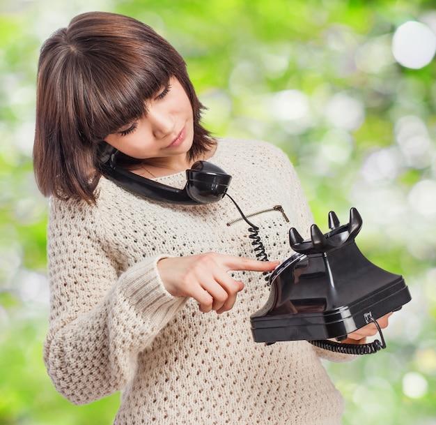 Vrouw die door een antieke telefoon