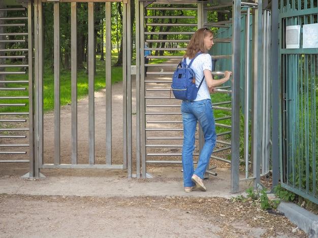 Vrouw die door een tourniquet naar een privépark gaat