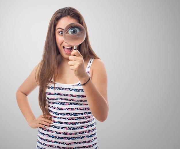 Vrouw die door een vergrootglas