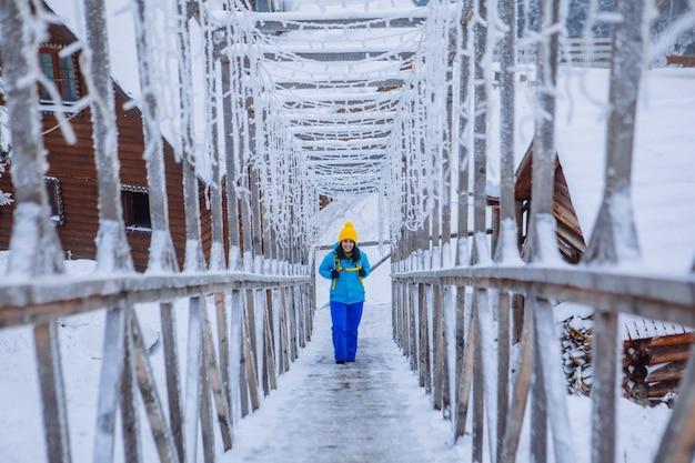 Vrouw die door ijzige besneeuwde trappen loopt in het winterbergresort, bergenresort