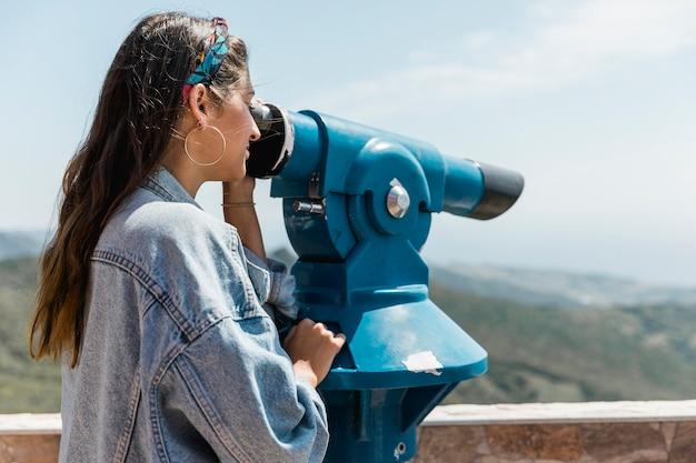 Vrouw die door muntstuk in werking gestelde verrekijkers op bergen kijkt