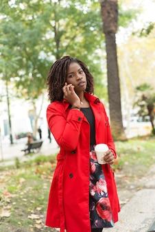Vrouw die door smartphone spreekt en kijkt