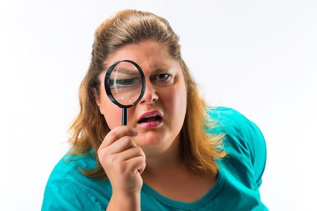 Vrouw die door vergrootglas of loupe kijkt