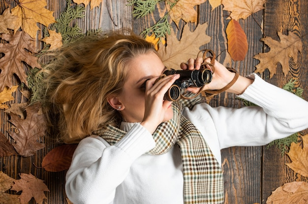 Vrouw die door verrekijkers kijkt. reizen vakantie reis concept. in de herfstbos. rondleidingen om vogels te spotten. koud seizoen concept. op zoek naar herfstwinkelverkoop. herfstseizoen ontdekken.