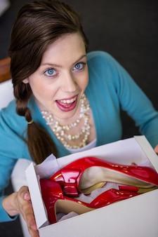 Vrouw die doos met rode schoenen toont