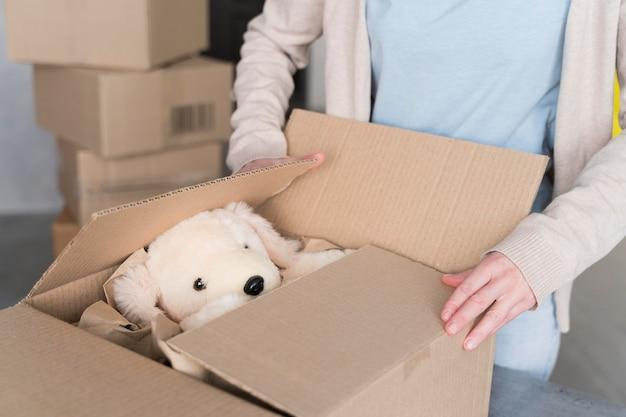 Vrouw die doos met te verzenden teddybeer voorbereidt