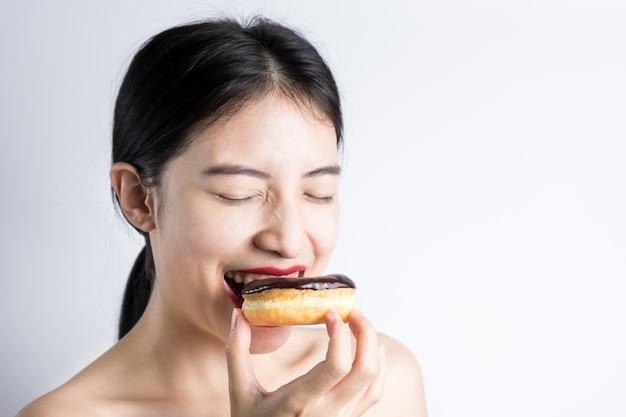 Vrouw die doughnut op witte achtergrond eet