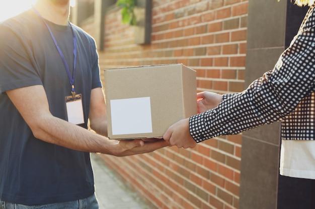 Vrouw die dozen ontvangt van de bezorger. lege doos