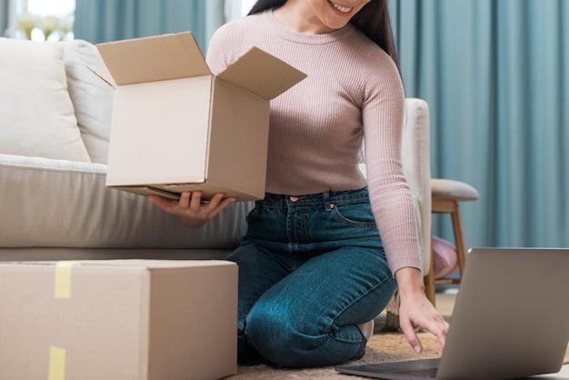 Vrouw die dozen opent die zij na online aankoop heeft ontvangen