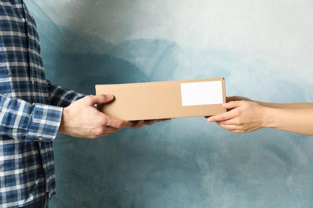 Vrouw die dozen van de leveringsman ontvangen tegen blauwe achtergrond, lege ruimte