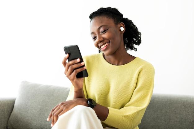 Vrouw die draadloze oordopjes draagt en een mobiele telefoon gebruikt