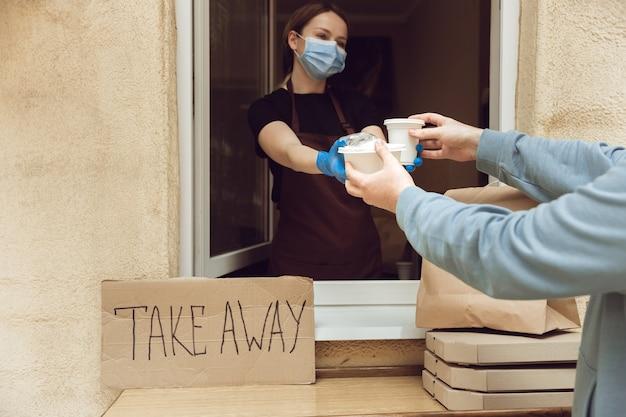 Vrouw die drankjes en maaltijden geeft aan de klant, met een beschermend gezichtsmasker en handschoenen. contactloze bezorgservice tijdens quarantaine coronavirus pandemie. afhaalconcept. recyclebare mokken, pakketten.