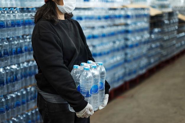 Vrouw die drinkwater draagt met gehandschoende handen tijdens de pandemie van het coronavirus