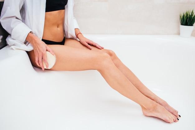 Vrouw die droge massage met natuurlijke borstel maakt. meisje dat in zwart ondergoed huidschil in de badkamers maakt. anti-cellulitis, afschilfering, huidverzorging concept. gezicht is niet zichtbaar.