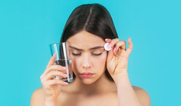 Vrouw die drugs gebruikt om hoofdpijn te verlichten. vrouw die pil tegen hoofdpijn neemt. brunette neemt wat pillen, houdt glas water, geïsoleerd op blauw.