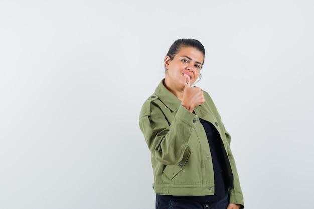 Vrouw die duim in jasje, t-shirt toont en vrolijk kijkt