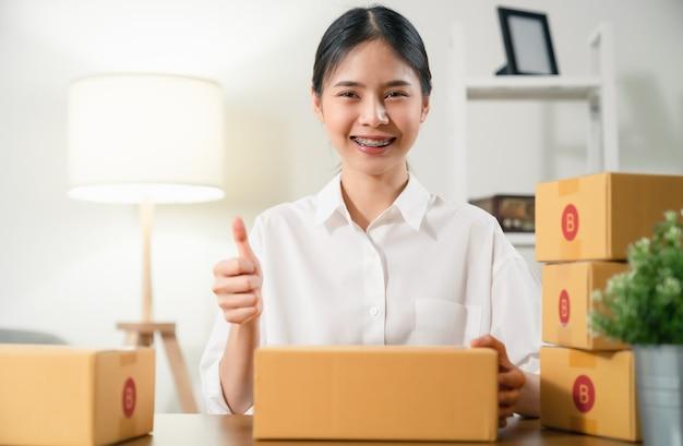 Vrouw die duim omhoog ondertekent en glimlacht tijdens het inpakken