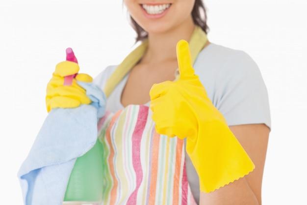 Vrouw die duimen opgeeft houdend schoonmakende producten
