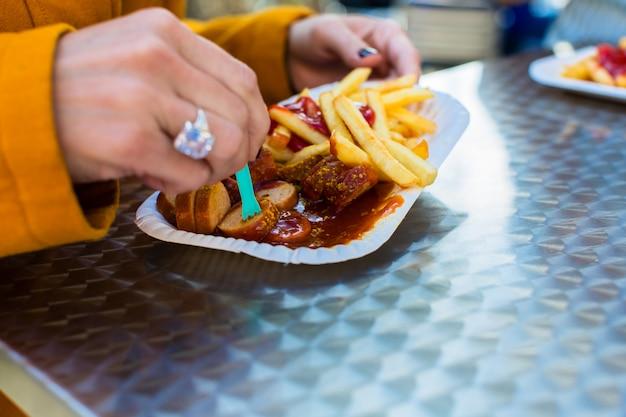 Vrouw die duitse currywurst eet bij de stand