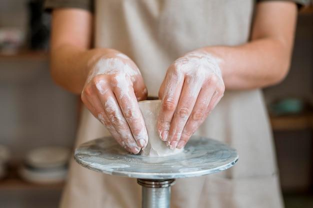 Vrouw die een aarden pot in haar atelier maakt