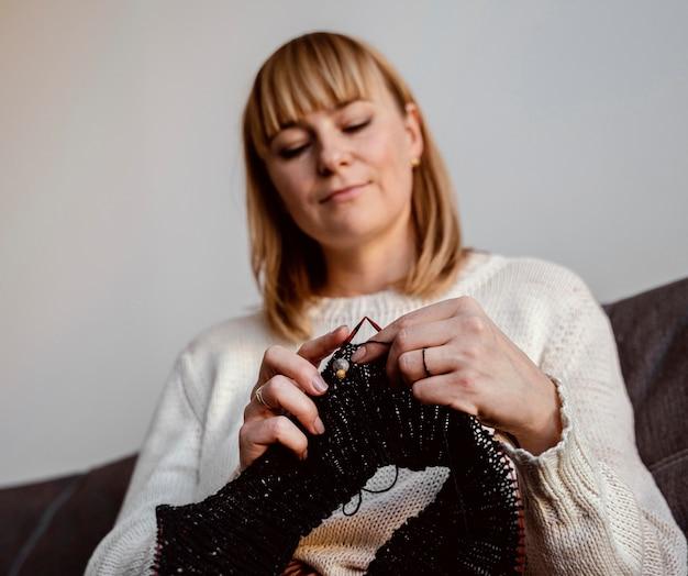 Vrouw die een accessoire van zwarte draad breit