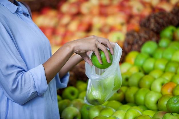 Vrouw die een appel koopt