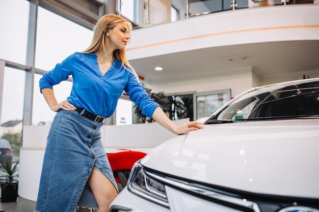 Vrouw die een auto in een autotoonzaal bekijkt