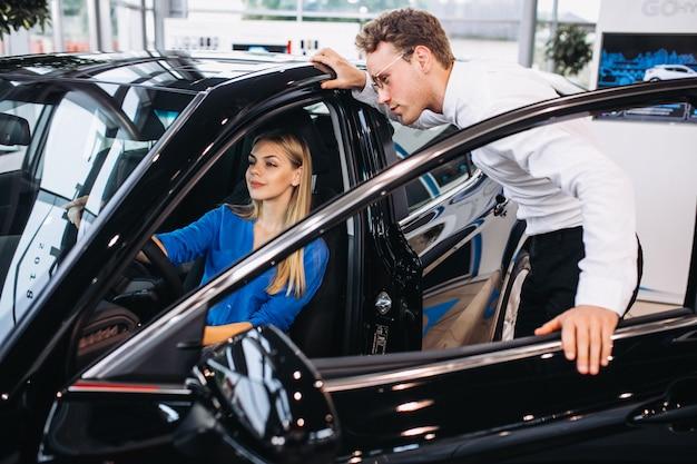 Vrouw die een auto in een autotoonzaal kiest