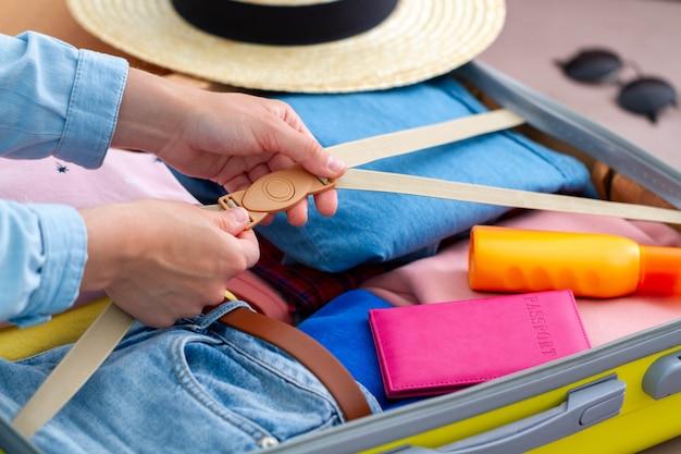 Vrouw die een bagage thuis voor een nieuwe reis en een reis inpakt. reizende koffer voor vakantiereizen en vakantie