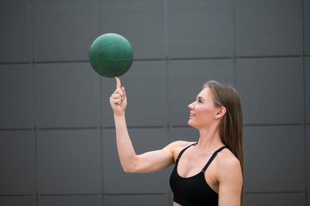 Vrouw die een bal op haar vinger middelgroot schot houdt