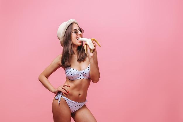 Vrouw die een banaan op een roze muur eet