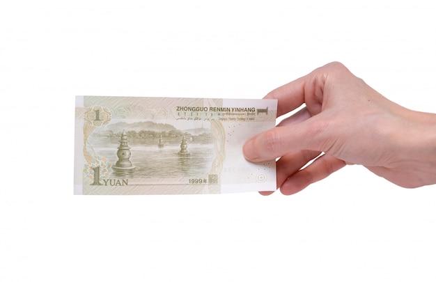 Vrouw die een bankbiljet van 1 chinees yuan in haar hand op een wit houdt