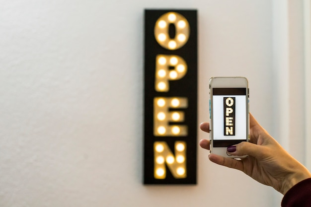 Vrouw die een beeld met mobiele telefoon nemen aan een open van de bedrijfs teken neonlichtwinkel decoratie. gloeilampen. horizontale weergave