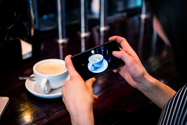 Vrouw die een beeld van koffie met smartphone in een koffie neemt