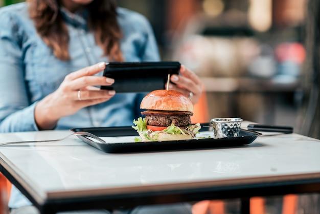 Vrouw die een beeld van voedsel op haar mobiele telefoon in het restaurant neemt. detailopname.