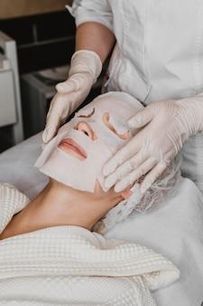 Vrouw die een behandeling van het huidmasker krijgt