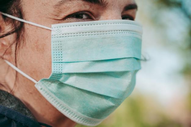 Vrouw die een beschermend chirurgisch masker draagt tegen ziekte covid-19