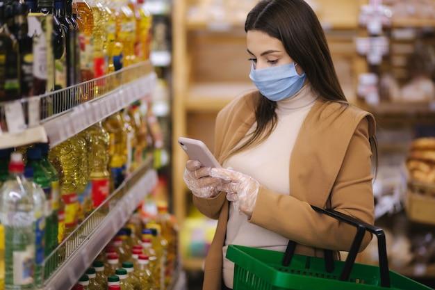 Vrouw die een beschermend masker en handschoenen in supermarkt draagt. winkelen tijdens de pandemische quarantaine