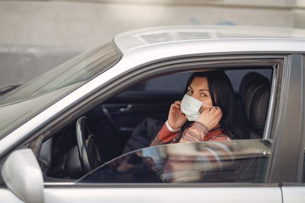 Vrouw die een beschermende maskerzitting in een auto draagt