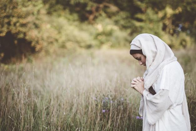 Vrouw die een bijbels gewaad draagt en bidt terwijl haar ogen gesloten zijn