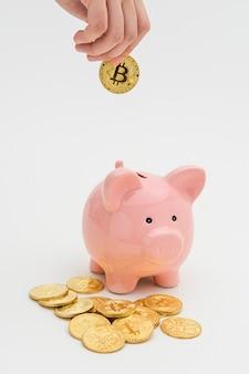 Vrouw die een bitcoin in een roze spaarvarken steekt