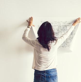 Vrouw die een blauwdruk op de muur opzet