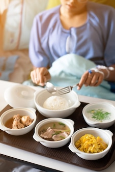 Vrouw die een blauwe jurk draagt, eet op het bed in het ziekenhuis