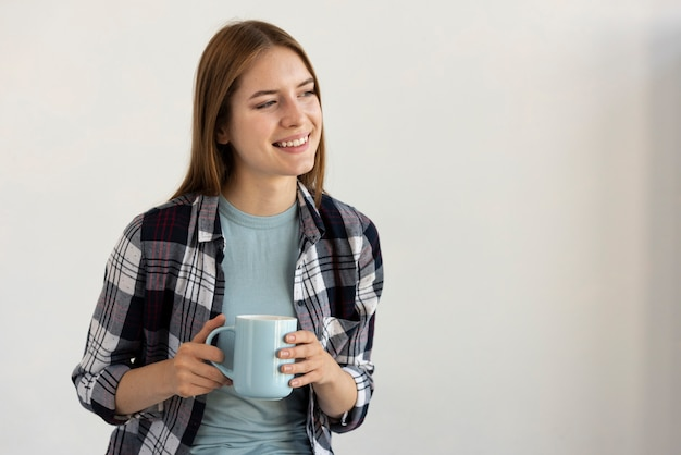 Vrouw die een blauwe kop van koffie houdt