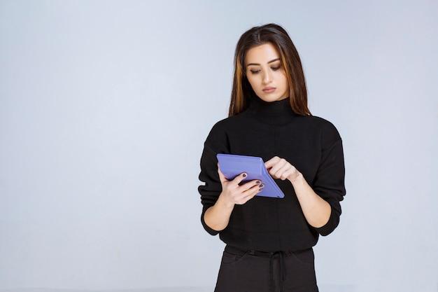 Vrouw die een blauwe rekenmachine vasthoudt en eraan werkt.