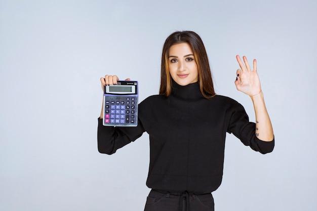 Vrouw die een blauwe rekenmachine vasthoudt en geniet van het eindresultaat.