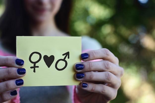 Vrouw die een blocnote, het concept van de gelijkheid van de gelijkheid toont.
