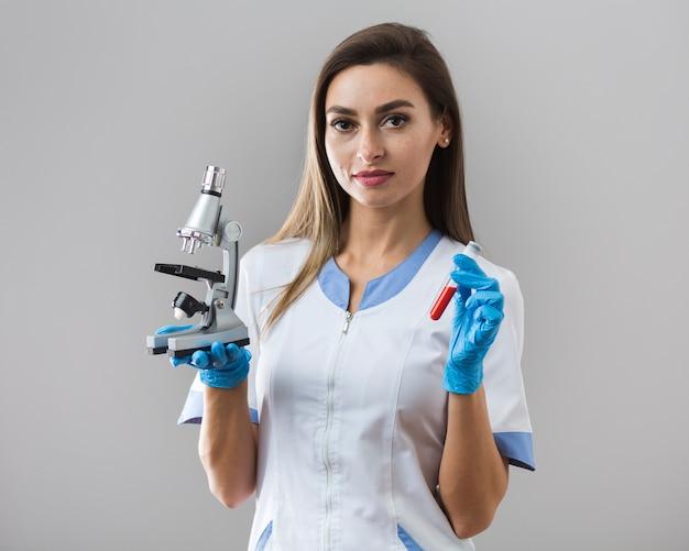 Vrouw die een bloedmonster en een microscoop houdt
